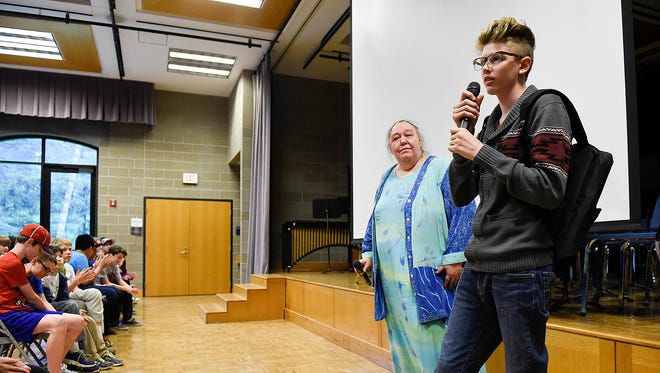 St. John's Preparatory School student Cullin Egge surprises Julia Dinsmore with $1,000 from the VING Project during an assemble Wednesday, May 11, at the school in Collegeville. Dinsmore is a poet and advocate for people experiencing poverty and/or homelessness.