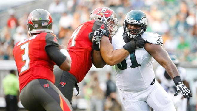 Eagles defensive tackle Fletcher Cox pushes past Tampa Bay's Ali Marpet en route to stripping the ball from quarterback Jameis Winston in the first quarter at Lincoln Financial Field Thursday.