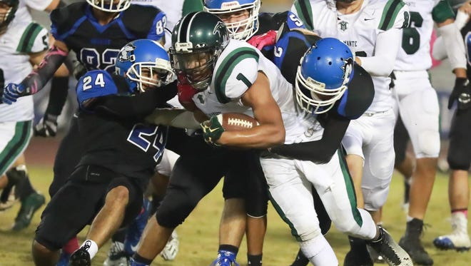 Hanford West's Noah Imperial (24) and Jacquez Marable (2) attempt to bring down El Diamante's Tyler Youngblood (1) during a game at Neighbor Bowl on Thursday.