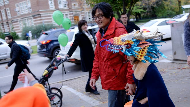 Yongjun Choi walks with his daughter Mercy, 7, on Thursday, Oct. 27, 2016 while trick or treating in downtown East Lansing.