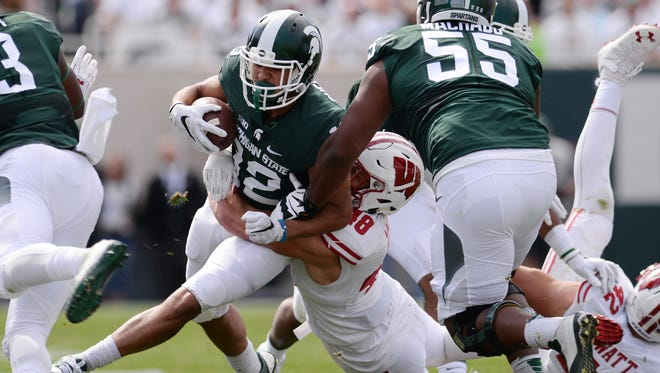 Senior wide receiver R.J. Shelton is brought down by Wisconsin's Jack Cichy during the 30-6 loss to Wisconsin on Saturday.