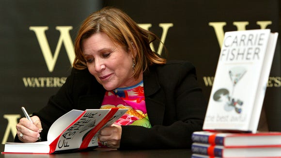 "FILE - In this Friday, Feb. 20, 2004 file photo, author Carrie Fisher autographs her new book ""The Best Awful"" at a promotional event in London. On Tuesday, Dec. 27, 2016, a publicist said Fisher has died at the age of 60. (AP Photo/John D. McHugh, File)"