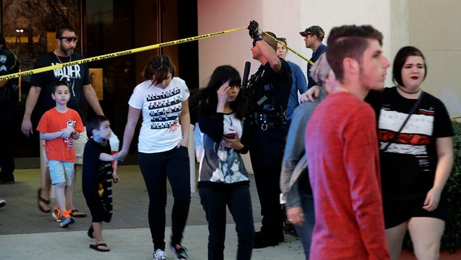 San Antonio police help shoppers exit the Rolling Oaks Mall after a deadly shooting Sunday, Jan. 22, 2017, in San Antonio.