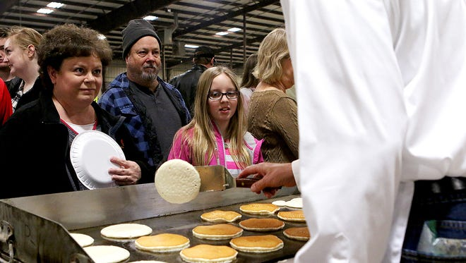 University Kiwanian Barry Macha talks with festivalgoers while cooking a batch of pancakes during the University Kiwanis Club's annual Pancake Festival Saturday morning at the J.S. Bridwell Agricultural Center.