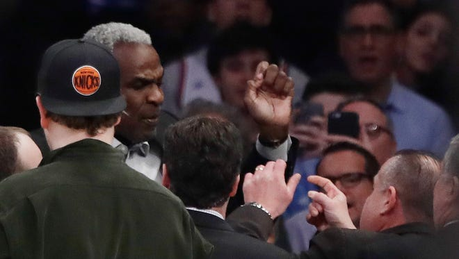 Former New York Knicks player Charles Oakley exchanges words with a security guard during Wednesday's game.