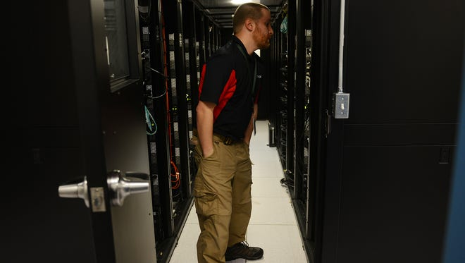 Rusty Allswede, a senior network administrator for Accident Fund, works in the data room of Accident Fund in Lansing. Area businesses are competing for people with Rusty's skills, stealing talent from one another,  as the region faces an IT talent shortage .
