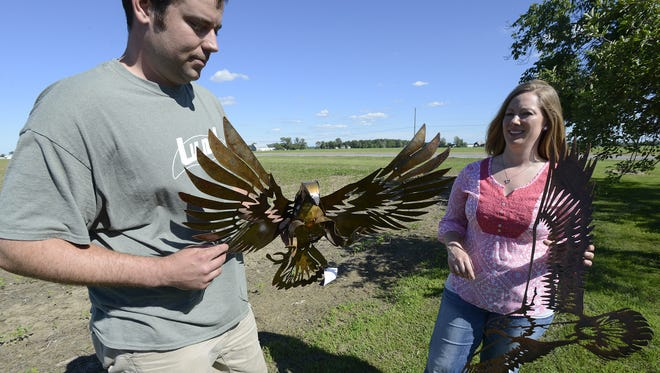 Jake, left, and Emily Zbierajewski of Imagine Metal Arts in Oak Harbor hold one of Jake's creations.