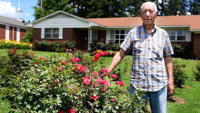 Clyde Freeman stands outside of his home in Jackson. Freeman's front lawn has over 250 rosebushes that he planted in honor of his late wife, Alta.