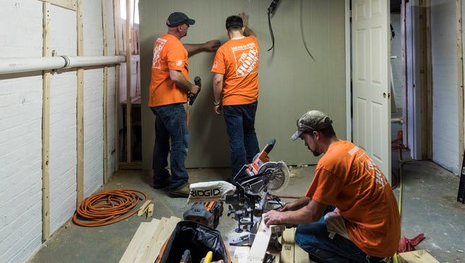 Home Depot employees Patrick Lynnville (left to right) and Vincent Beasley install HardieBacker, a cement backboard, along the basement walls as Andrew Seitz cuts pieces of wood to use for the basement steps during restoration event at the James Bethel Gresham Memorial Home in Evansville, Ind., on Thursday, June 29, 2017. Home Depot partnered with ECHO Housing to transform the home into temporary housing for veterans, where those residents will be offered help in acclimating to civilian life.