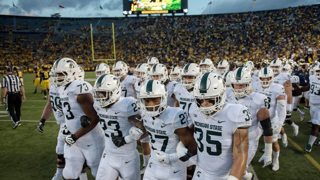 The Michigan State Spartans walk onto the field prior to their game against Michigan on Saturday, Oct. 7, 2017, at Michigan Stadium in Ann Arbor.