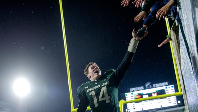 Michigan State quarterback Brian Lewerke celebrates with fans after the Spartans' 27-24 win over Penn State Saturday. Lewerke passed for 400 yards and two touchdowns.
