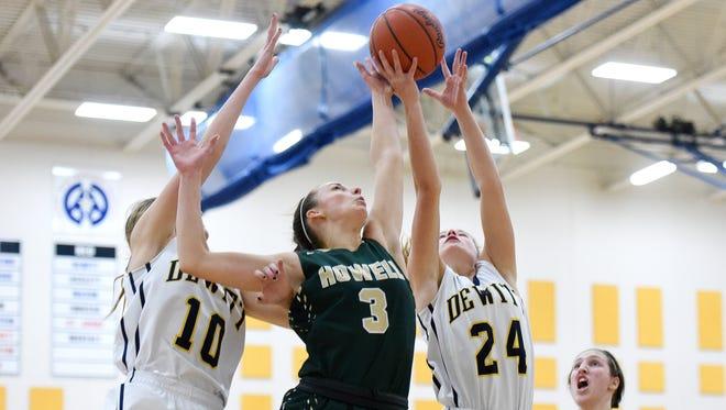 Howell's Amanda Corsten, center, goes up for a rebound between DeWitt's Sydney Mills, left, and Annie McIntosh during the fourth quarter on Wednesday, Jan. 3, 2018, at DeWitt High School. DeWitt won 40-36.