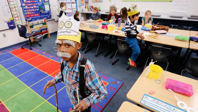 Sporting bushy grey eyebrows and a mustache, Hudson Allen, 7, walks with the aide of a cane Monday, January 29, 2018, in Shelly Williams' first grade classroom at Wyandotte Elementary School. Students, faculty and staff were celebrating the 100th day of the current school year with costumes and fun activities, including pretending they were 100 years old.