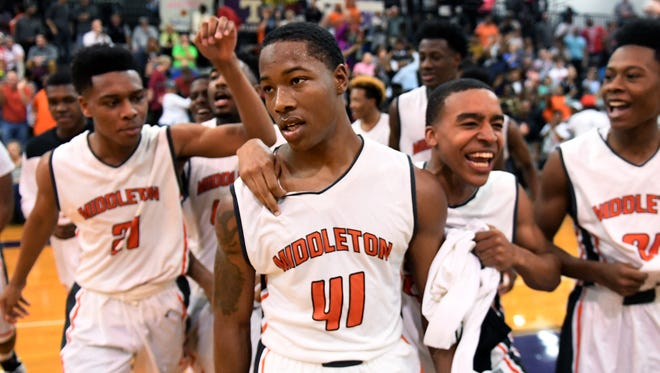 Middleton teammates celebrate with Maurius Reaves after his made a three point shot at the buzzer in overtime during the district 14-A Boys Championship game, Tuesday, Feb. 20. Middleton defeated Peabody, 62-59, to become the District 14-A Boys Champion.