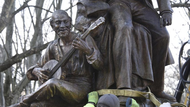 """A Pittsburgh Public work crew prepares to remove the Stephen Foster statue in Schenley Plaza on April 26, 2018, in Pittsburgh. The 118-year-old statue of the """"Oh! Susanna"""" songwriter was removed after criticism that the work is demeaning because it includes a slave sitting at his feet, plucking a banjo."""