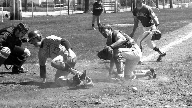 "From the looks of this photo from a 1977 baseball game between Algoma and Kewaunee high schools, there was a little confusion as Algoma's runner was coming home to score a run. The ball got loose, and a closer look at the Kewaunee players reveals their eyes weren't on the ball.  It wasn't that way for the Kewaunee team in 1894, when it walloped Two Rivers, 21-3. The first Nines — also called ""first string"" — played a game that was said to be interesting and played in a very gentlemanly manner throughout. Those who witnessed it said there were few kicks about the umpire and there was no shouting or yelling. Perhaps Two Rivers fans had all gone home.  The photo comes from the Heidmann Collection at the Algoma Public Library. Looking to find out more about baseball? Your local librarian will point you in the right direction."