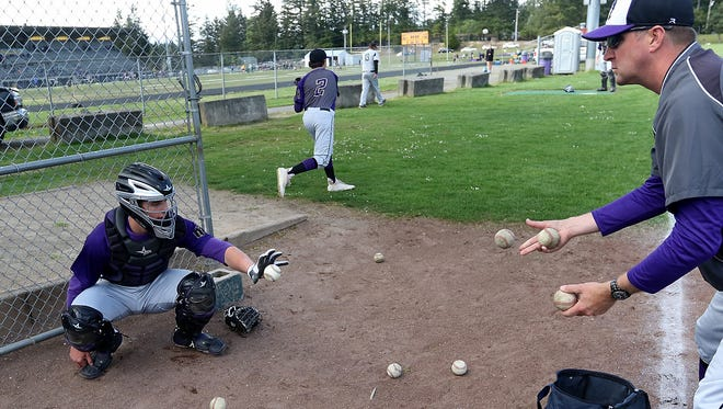 North Kitsap catcher Kyle Green warms up with his father Dave Green, a Vikings' assistant coach and former catcher, prior to the Vikings' game against Central Kitsap earlier this month.