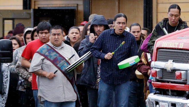 Native American drummers lead mourners out of a gymnasium following the memorial service for the 15-year-old gunman in a deadly Washington state school shooting nearly a week earlier, Thursday, Oct. 30, 2014, on the Tulalip Indian reservation, in Tulalip, Wash.