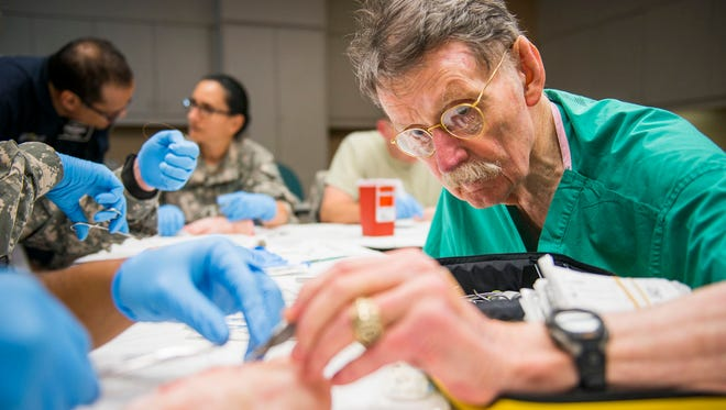 """Aug. 25, 2015: Dr. James """"Red"""" Duke instructs a group of U.S. Army flight medics in suturing techniques using pigs feet at Memorial Hermann Hospital in Houston on Aug. 15, 2013. Duke, a trauma surgeon who attended to Texas Gov. John Connally on the day of the Kennedy assassination before going on to become a familiar television doctor, died in Houston on Tuesday, at age 86."""