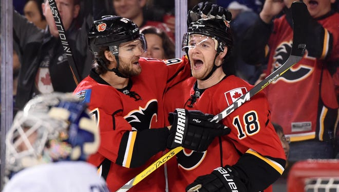 Flames center Matt Stajan, right, celebrates his first-period goal with right wing Michael Frolik at Scotiabank Saddledome.