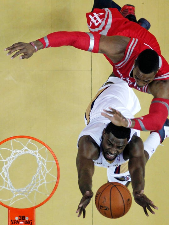New Orleans Pelicans forward Tyreke Evans goes to the basket against Houston Rockets center Dwight Howard, top right, in the first half of an NBA basketball game in New Orleans, Wednesday, April 16, 2014. (AP Photo/Gerald Herbert)
