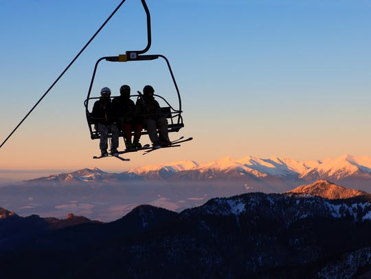 Chair ski lift with skiers over blue sky in the evening.