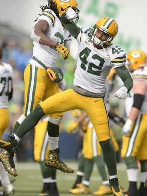 Green Bay Packers safety Morgan Burnett (42) celebrates with teammate Davon House (31) after Burnett recovered a fumble during Sunday's NFC Championship game against the Seattle Seahawks at CenturyLink Field in Seattle, Wash.