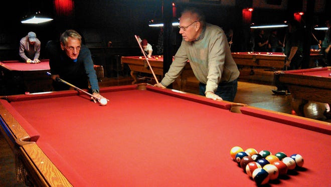 Mike Karnell of Coralville, left, and Rich Tyler of Iowa City start a game of eight ball at TCB Pool Hall on the pedestrian mall in downtown Iowa City.