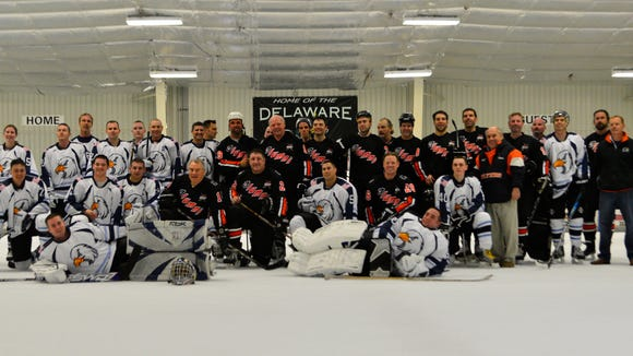The Dover Eagles and the Flyers Alumni hockey teams pose for a photo after their Apr. 12 charity hockey game at the Pond Ice Arena in Newark, Del. This was the third and final charity game of the season for the Eagles. (U.S. Air Force photo/Airman 1st Class William Johnson)