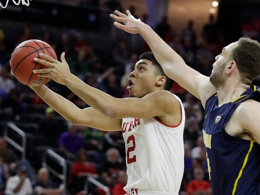 Utah's Sedrick Barefield shoots around California's Kameron Rooks during the first half of an NCAA college basketball game in the quarterfinals of the Pac-12 men's tournament Thursday, March 9, 2017, in Las Vegas. (AP Photo/John Locher)