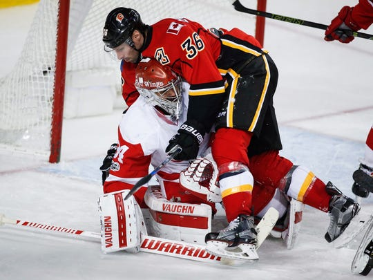 Red Wings goalie Petr Mrazek ducks as the Flames' Troy
