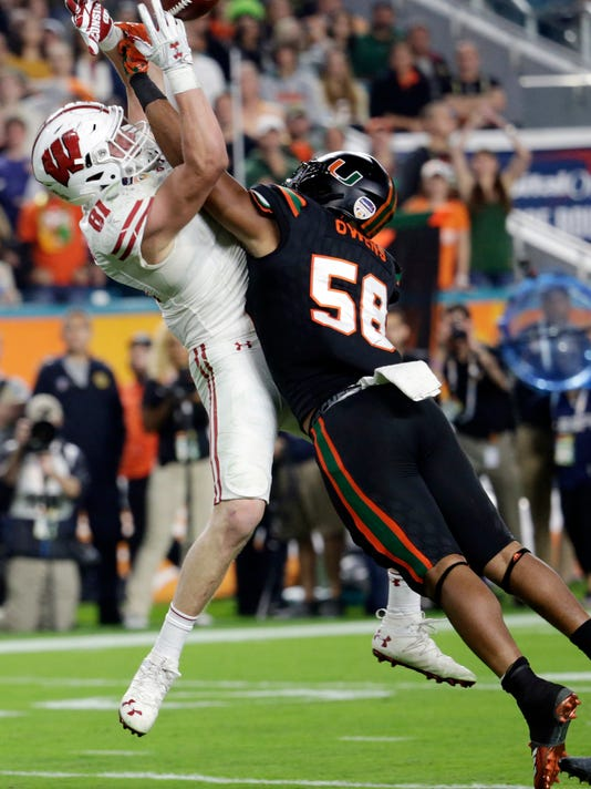 Miami linebacker Darrion Owens (58) defends Wisconsin tight end Troy Fumagalli (81), during the second half of the Orange Bowl NCAA college football game, Saturday, Dec. 30, 2017, in Miami Gardens, Fla. (AP Photo/Lynne Sladky)