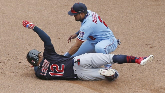 The Indians' Francisco Lindor, left, is tagged out at second base by Minnesota Twins second baseman Luis Arraez as he tried to stretch an RBI-single into a double in the fourth inning Sunday in Minneapolis.