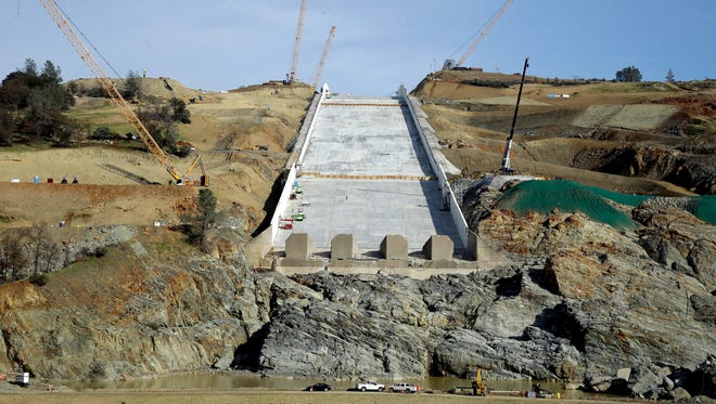 Cranes sit on the sides of the Oroville Dam spillway on Thursday in Oroville. California water officials and the construction manager said Thursday that recently found hairline cracks on the spillway are normal and expected in reinforced concrete because it shrinks as it cures.