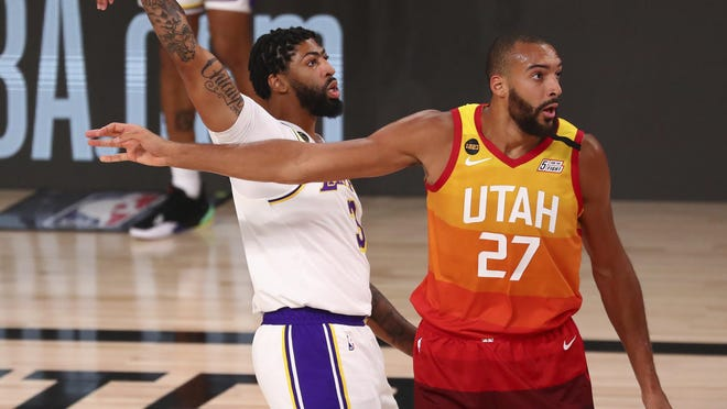 Los Angeles Lakers forward Anthony Davis (3) makes a three-point basket over Utah Jazz center Rudy Gobert (27) during the first half on Monday in Lake Buena Vista, Fla.