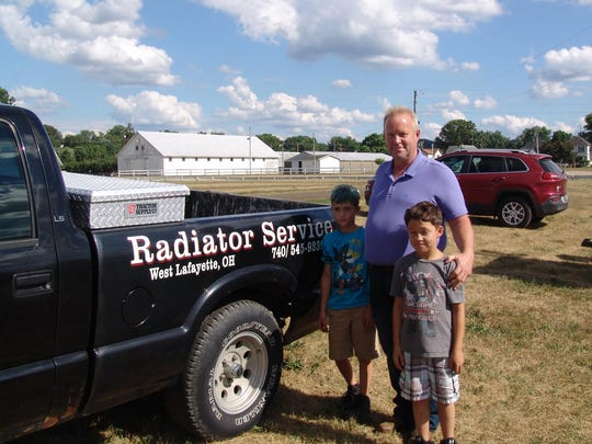 Steve Hall poses with his grandsons, Kholton and Kreston Smith, beside his company truck. Hall