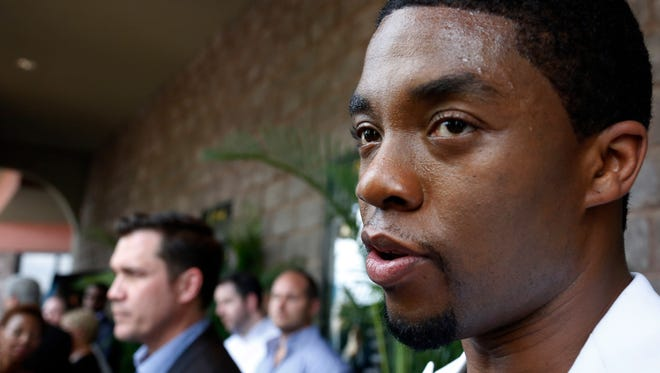 """Chadwick Boseman, right, who stars as James Brown in """"Get On Up,"""" a movie based on the life story of """"the Godfather of Soul,"""" speaks with a reporter while film director Tate Taylor, stands in the rear, in  Madison, Miss., prior to a screening of the film, Sunday, July 27, 2014. The film, directed by Mississippi native Taylor, depicts Brown's life from 5-years-old until he was 60. Brown died in 2006 at 73. (AP Photo/Rogelio V. Solis)"""