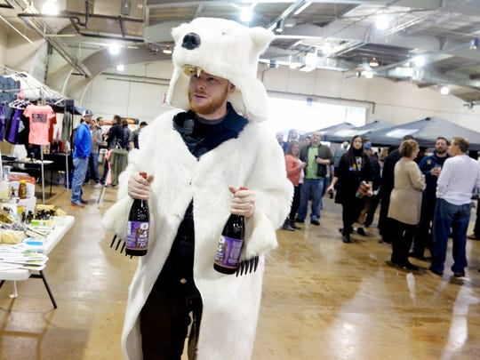 Hibrewnation co-founder Matthew Davis carries bottles of Lavery Brewing Company's Imperial French-Style Ale, aged in bourbon barrels, for a limited, timed release at the Hibrewnation craft beer festival on Saturday, Feb. 7, 2015, at the York Expo Center's Memorial Hall.