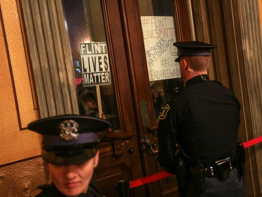 Protestors bang on the doors of the Michigan State Capitol Building in Lansing on Tuesday, January 19 while shouting for the removal of Governor Rick Snyder for his administration's role in the Flint water crisis before Snyder's State of the State address.