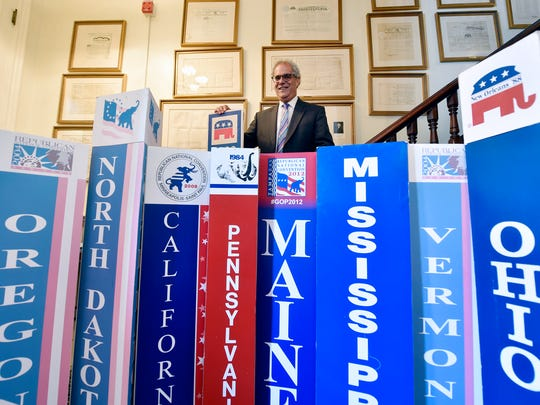 Charlie Gerow, a political consultant who will be an alternate delegate for the 4th Congressional District to the Republican National Convention in Cleveland, stands in his Harrisburg office Wednesday, July 13, 2016, for a portrait with state standards he has collected from various national conventions. Gerow has attended every Republican National Convention since 1976.