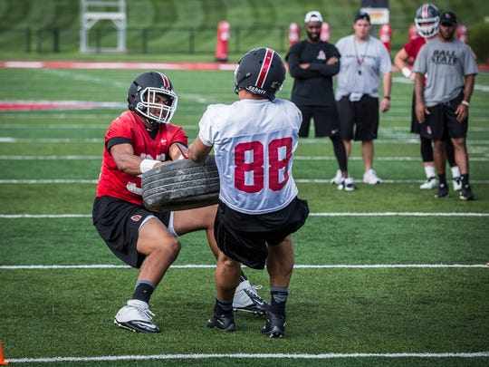 True freshman Nolan Givan compete in a tire pulling competition during practice at Scheumann Stadium.