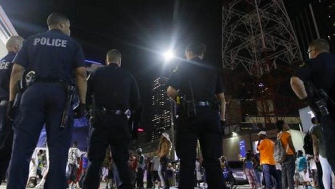 Dallas police officers gather in the early-morning hours Friday, after at least five officers were killed and others wounded by a sniper.