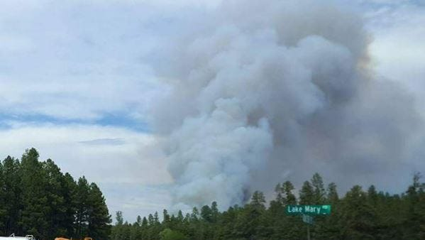 A plume of smoke rises from the Tank Fire, burning about 20 miles north of Payson in the Coconino National Forest on June 14, 2018.