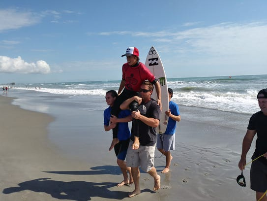 Eithan Osborne of San Clemente, Calif., is carried