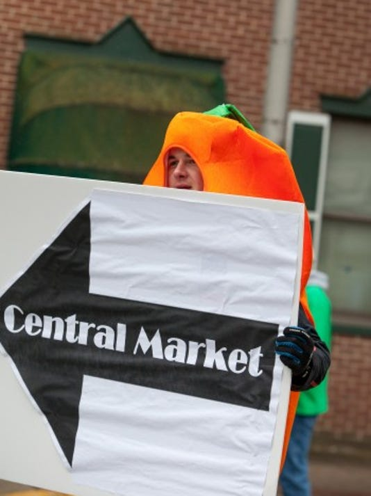 While dressed as a vegetable during the York St. Patrick's Day Parade, Kip Robson hands out Family First Health Greenbacks, which were 'dollars' that could  be used at Central Market York to buy fruits and vegetables. (Submitted)