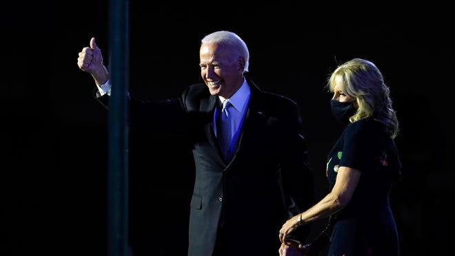 President-elect Joe Biden stands on stage with his wife Jill Biden as he gives the thumbs-up to the cheering crowd beyond the protective glass, Saturday, Nov. 7, 2020, in Wilmington, Del.