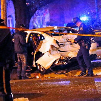 Police talk to a man sitting in a car that was struck