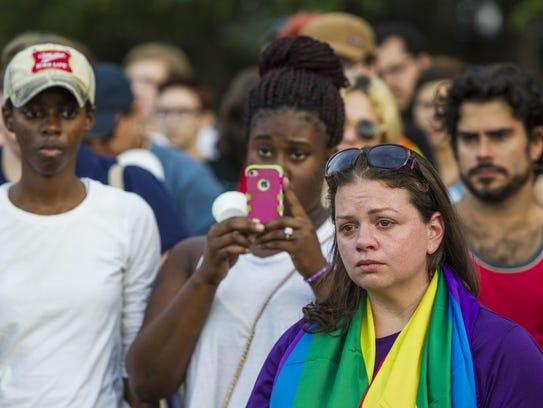 Carla McClellan, 32, tears up as she listens to speakers