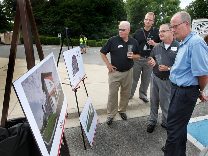 Steve Koenen, left, and Dan Schwaab with Altra Federal Credit Union, talk   with Jeff Harris and Phil Harpel about the renderings of the new location for the Altra Federal Credit Union during Clarksville Area Chamber of Commerce Business After Hours which was hosted by Altra Federal Credit Union at 1600 Madison Street location. Altra plans to start construction on a new building on Wilma Rudolph Blvd. in the fall.