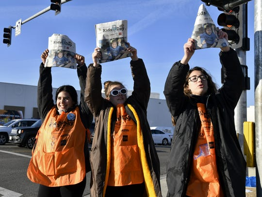 Golden West High School students Sierra Loya, Kelby Keeling and Cameron Smith sell Kids Day newspapers on Mooney Boulevard Tuesday morning.
